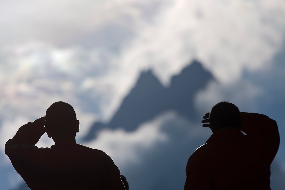 Buddhist monks shield their eyes from the sun as they look out towards Khumbi Yul Lha rising above Tengboche Monastery at sunrise in Khumbu (Everest) region, Sagarmatha National Park, Himalaya Mountains, Nepal.