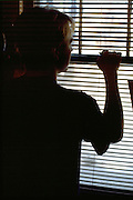 Silhouette of depressed college student age 20 at window.   St Paul Minnesota USA