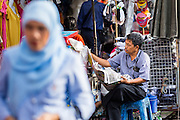 06 JUNE 2013 - BANGKOK, THAILAND:     A Thai Muslim woman walks past a vendor reading his newspaper in Bobae Market in Bangkok. Bobae Market is a 30 year old market famous for fashion wholesale and is now very popular with exporters from around the world. Bobae Tower is next to the market and  advertises itself as having 1,300 stalls under one roof and claims to be the largest garment wholesale center in Thailand.       PHOTO BY JACK KURTZ
