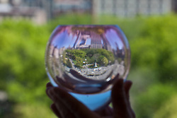 Union Square Park reflected in a hand held glass container in New York City