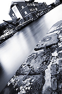 A slow shutter, long exposure picture taken in Leeds city center, United Kingdom, over the water from the stone jetties, to the Investec building behind the canal boats, which shimmer off the fast moving high water.