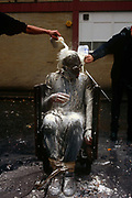 In a London street, an apprentice in the bakery or milk industry endures a shower of fresh milk being poured over his head after a dusting of flour. This traditional ritual is usually performed on the unfortunate young man when he has successfully passed his apprenticeship term in the company - his mates participating in making his day as miserable as possible. But he takes it with good humour as it means he is now initiated into the industry.