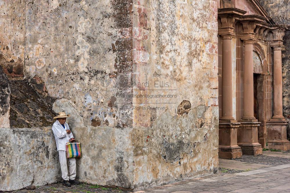 A Mexican farmer rests against a wall at the Templo del Sagrario in Patzcuaro, Michoacan, Mexico.