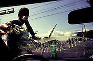 Young man working on the street of Dominican Republic, cleans windshields to make a living.