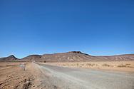 Desert landscape with street and mountains against clear blue sky near Tagounite, Sahara desert, Morocco.