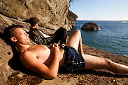 Henry (front) and Zach Podell-Eberhardt relax in a rock alcove waiting for sunset at Cullite Cove, West Coast Trail, British Columbia, Canada.