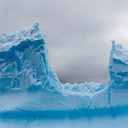 Icebergs carved into jagged shapes in an iceberg graveyard in a cove at Melchior Island on the western side of the Antarctic Peninsula.