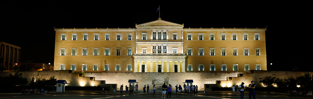 Syntagma square. Athens. Greece. Night view of the lit up neoclassical façade of the Greek Parliament building opposite Syntagma Square in Athens. The building also known as Vouli was erected in 1836-42 and was originally the Royal Palace. Below the building is the monument to the Unknown Soldier, erected in 1929-1932, it depicts a relief of a dying Greek solider modelled on a figure from the pediment of the Temple of Aphaia at Aegina.  The monument is guarded around the clock by two elite members of the Presidential ceremonial guard unit known as Evzones.