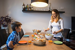 Pregnant mother preparing salad on the dining table, while son watches, Munich, Germany
