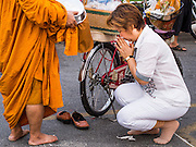 "14 FEBRUARY 2014 - BANGKOK, THAILAND:  A woman presents alms to a monk on Makha Bucha Day at Wat That Thong (also called Wat Tad Tong) in Bangkok. The aims of Makha Bucha Day are: not to commit any kind of sins, do only good and purify one's mind. It is a public holiday in Cambodia, Laos, Myanmar and Thailand. Many people go to the temple to perform merit-making activities on Makha Bucha Day. The day marks four important events in Buddhism, which happened nine months after the Enlightenment of the Buddha in northern India; 1,250 disciples came to see the Buddha that evening without being summoned, all of them were Arhantas, Enlightened Ones, and all were ordained by the Buddha himself. The Buddha gave those Arhantas the principles of Buddhism, called ""The ovadhapatimokha"". Those principles are:  1) To cease from all evil, 2) To do what is good, 3) To cleanse one's mind. The Buddha delivered an important sermon on that day which laid down the principles of the Buddhist teachings. In Thailand, this teaching has been dubbed the ""Heart of Buddhism.""   PHOTO BY JACK KURTZ"