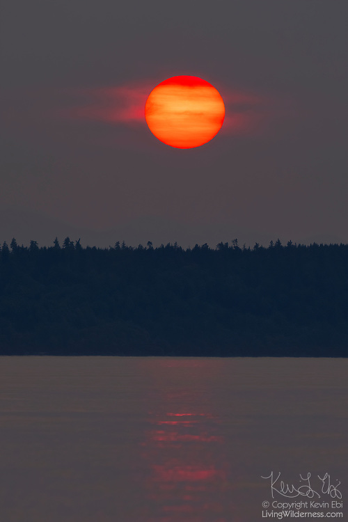 Partially obscured by a smoky haze from wildfires, the sun prepares to set behind Whidbey Island in this view from Edmonds, Washington.