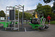Men working out on outdoor gym equipment in Burgess Park on 17th September 2015 in South London, United Kingdom. On the horizon is the Aylesbury Estate, a large housing estate located in Walworth, South East London. It contains 2,704 dwellings and was built between 1963 and 1977. The whole estate is currently undergoing a major redevelopment with most of the dwellings are derelict.