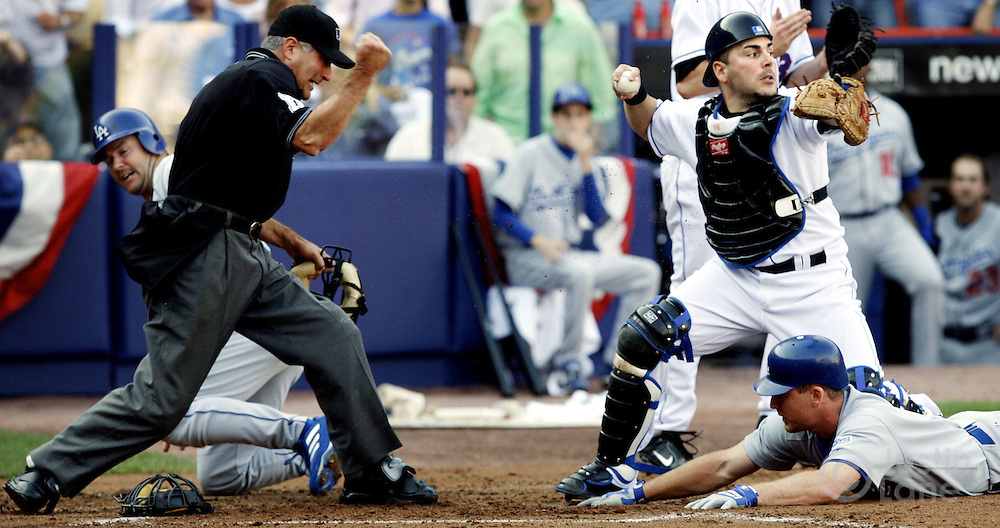 New York Mets catcher Paul Lo Duca is seen after tagging out the Los Angeles Dodgers' J.D. Drew (R) and Jeff Kent (L) at home plate during the National League Division Series between at Shea Stadium on Wednesday 04 October 2006.