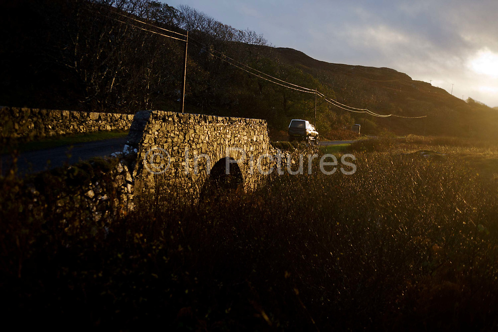 A farm vehicle drives in winter light over the traditional stone bridge built from locally sourced materials over the Allt an Eas River at Eas Falls, near Kilbrennan, Isle of Mull, Scotland. Beneath the bridge is the fast-flowing river that curls downhill, falling steeply into the distant Loch Tuath with the Island of Ulva, the headland beyond. Eas Fors Waterfall is one of the most spectacular waterfalls on the island, situated just off the B8073, a couple of miles North of Ulva Ferry. Eas is Gaelic for waterfall, Fors is Norse for waterfall and the final fall plunges 100 feet over the edge of the cliff to the sea below.