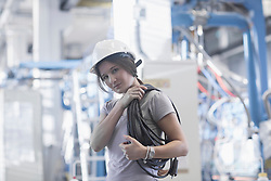 Portrait of a female technician carrying coil of rope on shoulder in an industrial plant, Freiburg Im Breisgau, Baden-Württemberg, Germany
