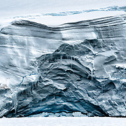 A vertical cliff of glacial ice reveals the layers of its creation on the Antarctic Peninsula.