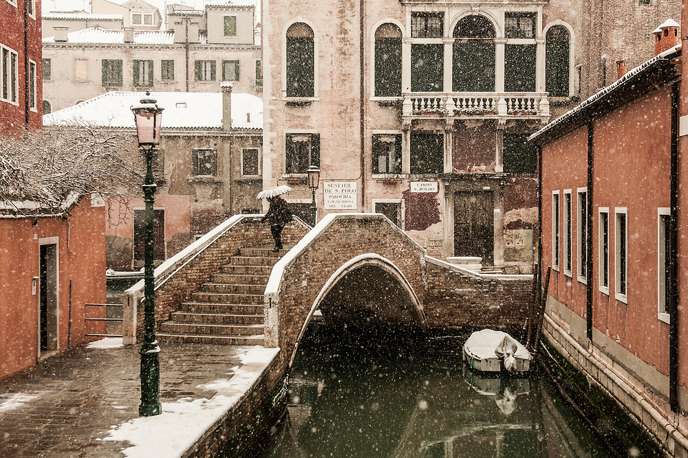 """VENICE, ITALY - 28th FEBRUARY/01st MARCH 2018<br /> A woman crosses a bridge during a snowfall in Venice, Italy. A blast of freezing weather called the """"Beast from the East"""" has gripped most of Europe in the middle of winter of 2018, and in Venice A snowfall has covered the city with white, making it fascinating and poetic for citizen and tourists.   © Simone Padovani / Awakening"""