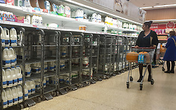 © Licensed to London News Pictures. 27/10/2021. London, UK. A shopper walks past nearly empty shelves of milk in Sainsbury's, north London, as food shortages continue, following Brexit. According to the British Retail Consortium, three in five retailers expect prices to increase in the run up to Christmas, and the ongoing labour shortages are making the situation worse. Photo credit: Dinendra Haria/LNP