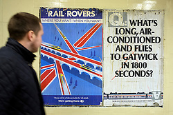 © Licensed to London News Pictures. 03/12/2011, London, UK. A man walks past a poster advertising the Gatwick Express service from Victoria Station in Central London.  Staff working at Richmond Station in London have uncovered railway posters from the late 1980's whilst upgrading poster holders. Photo credit : Stephen Simpson/LNP