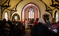 Parishoners stand as Bishop A. Robert Hirschfeld begins the final service at Trinity Episcopal Church in Tilton on Sunday afternoon.  (Karen Bobotas/for the Laconia Daily Sun)
