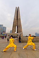 Chinese  man and woman practicing tai chi in the early morning in Huangpu Park, Shanghai, China