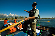 PRICE CHAMBERS / NEWS&GUIDE<br /> Barker-Ewing Float Trips Guide Nick Huckin points out some interesting features of the Snake River as guests enjoy the relaxing float.