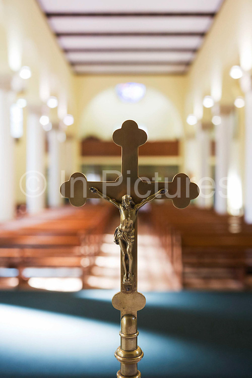 A Christian crucifix on the altar at St. Lawrence's Catholic church in Feltham, London. With bright summer light flooding the interior of this church through the Clerestory, the row of windows, high up towards the church roof, on either side of the central aisle. Built in the 1930s, we see the church's depiction of the crucifixion of Jesus on the cross, the image of martyrdom for Christians the world over. In the background are the church pews that accommodate the congregation - the central aisle in the middle of the picture - and the high arches of the main Nave (the wide, main body of a church building).