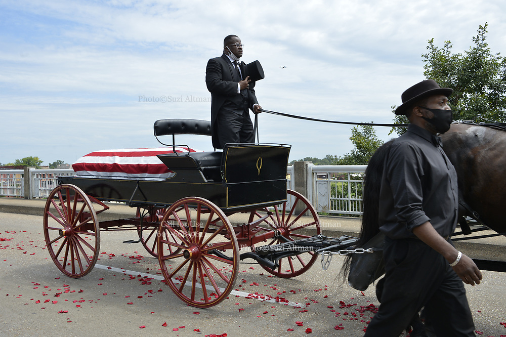 7/26/2020 SELMA/Alabama - John Lewis's family is seen walking behind the casket over the Edmund Petus Bridge, and then once over they are seen placing roses on the casket. The United States honor Guard carry the casket of Civil Rights Icon and Congressmen John Lewis from the horse the horse drawn carriage that just crossed the Edmund Pettus Bridge for the last time into the casket to head to the State Capitol, where he will lay in state.. A horse drawn carriage from Watkins Funeral Home in Atlanta leads the flag draped casket of Civil Rights icon and Congressman John Lewis over the Edmund Pettus Bridge for the last time.The rose petals represent the blood shed from Bloody Sunday in 1965 where Lewis was beaten by police and ended up with a  fractured skull. On the anniversary of President Lyndon Johnson signing the Voting Rights Act, Congressman John Lewis's casket is pulled by a horse drawn carriage  across the Edmund Pettus Bridge in Selma for the last time. The casket is headed to the State Capitol in Montgomery where he will lay in state and then will head to Washington DC and then to his final resting place in Atlanta Georgia.  Photo© Suzi Altman