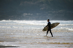 A surfer carries his surfboard as he walks out of the sea at Fistral Beach in Newquay, Cornwall.