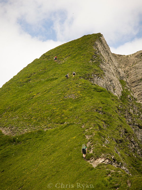 Hikers scaling steep mountainside in the west Austrian Alps