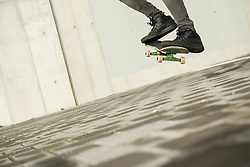 Low section view of a man jumping with skateboard in mid-air, Munich, Bavaria, Germany