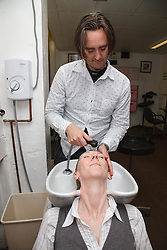 Hairdresser who has Ehlers-Danlos Syndrome (EDS), helped into employment by the Ready 4 Work team, Nottinghamshire County Council, washing a woman's hair