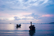 Traditional Thai longtail boats at sunset in the Andaman Sea at Railay West Bay, Railay.