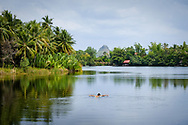 A boy is bathing in the tropical Kampong Bay river near the village of Kampot in southeastern Cambodia