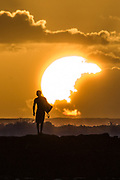 A surfer walks along the breakwall in Waikiki at sunset.