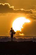 A surfer walks along the breakwall in Waikiki at sunset.