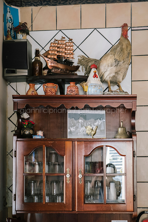 NAPLES, ITALY - 1 AUGUST 2018: Interior decorations are seen here at Cantina del Gallo, a family-owned restaurant in the Rione Sanità in Naples, Italy, on August 1st 2018.<br /> <br /> Cantina del Gallo, in the Rione Sanità, was established in 1898 and run by four generations of the Silvestri family. The cantina began as a store selling bulk wine and oil. It was only in the 1950s, when the legendary Aunt Cuncetta began cooking, that it became the simple and genuine tavern it is today.<br /> There are three dishes that are the restaurant's workhorses, and the ones we always seem to rotate between: the pennette alla sorrentina (a variation of the classic gnocchi alla sorrentina, seasoned with tomato, basil and stringy mozzarella), the baked cod (although the fried cod is just as mouth-watering) and the pizza cafona (peasant pizza), topped with oregano, cheese, chile and with double the tomatoes (tomato juice and chopped tomatoes).