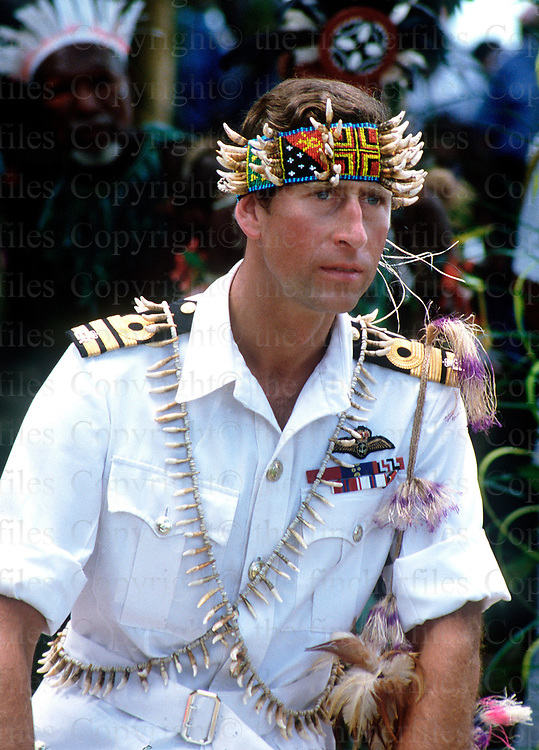 The Princes of Wales wears a traditonal costume with his naval uniform during a visit to Papua New Guinea in 1984. Photographed by Terry Fincher