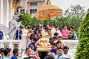 12 APRIL 2013 - BANGKOK, THAILAND:   .Bangkok Governor Sukhumbhand Paribatra, lower left, helps carry the Phra Buddha Sihing to a waiting truck.  The Phra Buddha Sihing, a revered statue of the Buddha, is carried by truck through the streets of Bangkok so people can make offerings and bathe it in scented oils. Songkran is celebrated in Thailand as the traditional New Year's Day from 13 to 16 April. The date of the festival was originally set by astrological calculation, but it is now fixed. If the days fall on a weekend, the missed days are taken on the weekdays immediately following. Songkran is in the hottest time of the year in Thailand, at the end of the dry season and provides an excuse for people to cool off in friendly water fights that take place throughout the country. The traditional Thai New Year has been a national holiday since 1940, when Thailand moved the first day of the year to January 1. The first day of the holiday period is generally the most devout and many people go to temples to make merit and offer prayers for the new year.  PHOTO BY JACK KURTZ