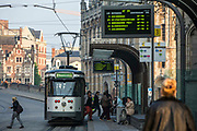 Passengers disembark from a De Lijn tram at Korenmarkt 3 stop in the historical centre of Ghent, Belgium.