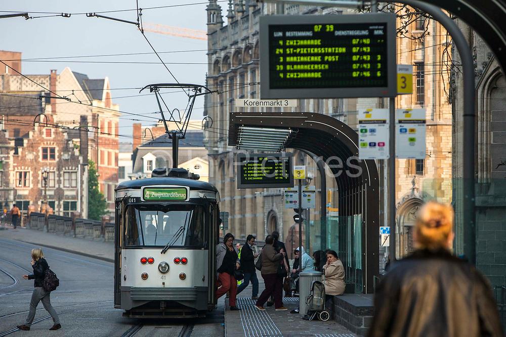 Passengers disembark from a De Lijn tram at Korenmarkt 3 stop in the historical centre of Ghent, Belgium.