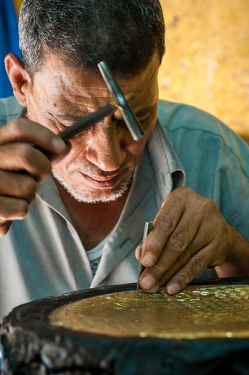 An Egyptian man at a workshop in Islamic Cairo, in a neighborhood behind the Khan el-Khalili Bazaar, works on a copper plate to create a beautiful design. The job will take at least two days. Sunlight from an open door is on his face. (May 2010)