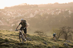 Young men mountainbiking at sunrise, Bavaria, Germany