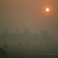 Dawn over fields of haystacks.