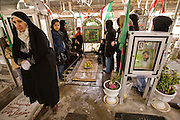 A family memorializes a family member killed during the Iran-Iraq War (1980-1988) in the Martyr's section of the Behesht Zahra cemetery in Tehran, Iran. Other parts of the cemetery are devoted to the rest of the population. Memorializing family members who have died is an important part of Islamic and Persian culture in Iran and follows a prescribed series of graveside visits. Iranians meet at the graves, bringing food to share with each other and passersby who pay their respects.