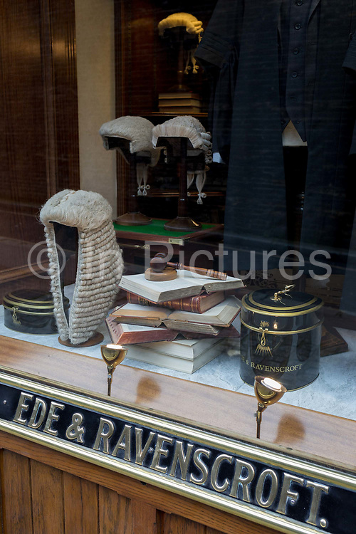 Court dress wigs for the legal profession barristers and judges in the window of Ede & Ravenscroft, on 15th February 2017, in London, United Kingdom. Ede & Ravenscroft is thought to be the oldest firm of tailors in the world. In 1689, the area of London now known as Aldwych, was the bustling centre of the tailoring trade. They have been tailors and robemakers of choice for twelve coronations. Today the firm continues to service royalty, the judiciary, civic authorities, academia and business.