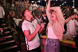 © Licensed to London News Pictures. 07/07/2021. London, UK. England fans celebrate at Tobacco Dock after Harry Kane scores a penalty in the Euro 2020 semi-final between England and Denmark. Photo credit: Rob Pinney/LNP