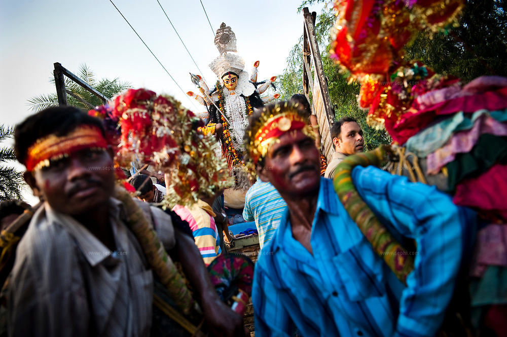 An idol of the HIndu goddess Durga being transported on the back of a truck to the site of immersion during the Durga Puja festival, some forty km from Delhi, Spetember 2009
