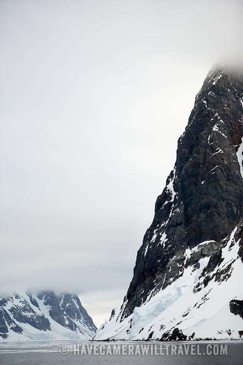 """Steep rocky cliffs rise out of the water along the narrow Lemaire Channel on the western side of the Antarctic Peninsula. The Lemaire Channel is sometimes referred to as """"Kodak Gap"""" in a nod to its famously scenic views."""