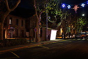 The promonade of Lagrasse with Christmas lights and bus shelter on 10th December in Lagrasse, France. The night landscape is rapidly changing with the development of bright LED lighting.